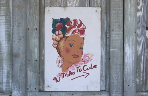 "Photograph of a sign taken in Key West, Florida. The sign reads ""90 Miles to Cuba."" The illustration above the text portrays a Carmen Miranda-like Cuban woman's head and face. She wears a fruit hat with green leaves and a large red and white bow on the front. The illustration depicts a woman with rosy red cheeks, full red lips, heavily mascarad blue eyelids, and pencil thin eyebrows. Her head is cocked at a slight angle as she appears to be looking over her left shoulder. The white background of the sign contrasts with the faded gray and white boards upon which the sign has been nailed."