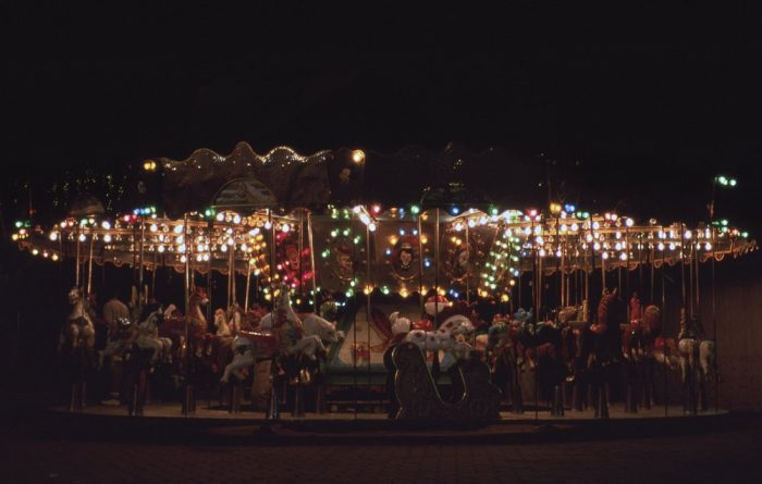 A dark, underexposed landscape photo of a carousel at night in Acapulco, Mexico. The full width of the motionless, empty carousel fills the frame horizontally, with black sky in the upper third of the image. Beneath the canopy, softly glowing white, green, blue, and red 3-inch round decorative lightbulbs cast a faint sheen onto the brass poles below, which thread dimly lit vacant horses hovering over the floor. The deserted carousel, which should be rotating with loud music and filled with smiling happy children, instead conveys a ghostly quiet stillness.