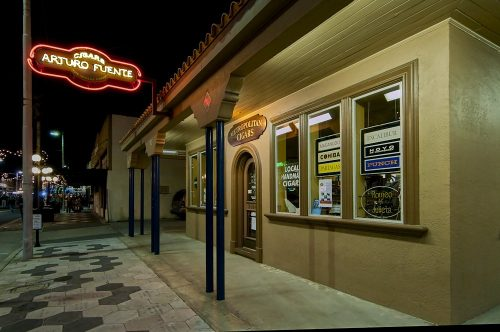 "Landscape photo of the Arturo Fuente cigar store in Ybor City, at night. We see the building at an angle, as the photograph was taken from the right-front side of the store looking down the sidewalk to the left. Incandescent lights underneath a four-foot-wide overhang, supported by three pairs of black metal posts, illuminate the storefront in a warm glow. An oval-shaped neon sign protrudes perpendicularly from the tiled roof, in front of a black night sky, proclaiming: ""Cigars, Arturo Fuente"" in yellow neon, surrounded by a red neon border. The sidewalk is vacant underneath Ybor City's globe-clustered streetlights which are visible down to the horizon."