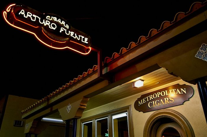 """Landscape photo of the Arturo Fuente cigar store in Ybor City, at night. The store front's Mediterranean tiled roofline angles from the upper right corner down to the lower left corner of the image. In the upper left corner of the image, an oval-shaped neon sign angles 45-degrees out from the tiled roof. The roofline and sign form an X, framed by a dark black sky. The sign proclaims: """"Cigars, Arturo Fuente"""" in yellow neon letters, surrounded by a red neon border. In the lower right third of the image an oval varnished wooden sign states """"Metropolitan Cigars"""" in yellow letters over the top of a rounded, arched wooden door frame."""