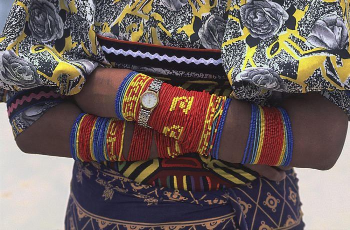 A close-up landscape photo of a Kuna woman in the Guna Yala region of Panama. The top of the frame starts just below her shoulders and continues several inches below her waist. Arms folded at her waist, each arm is wrapped with a single strand of colorful beads, with clusters of blue, red, and yellow sections. A watch is strapped over the wrist of her topmost arm. Her yellow print blouse displays large gray flowers outlined in black, with black leaves surrounding the buds. Her dark blue skirt features large beige-colored abstract patterns. She is a showcase of multiple colors.