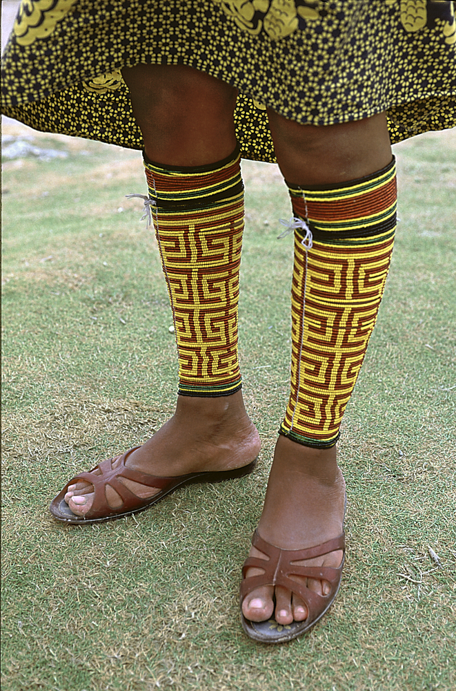 Vertical photograph of a young Kuna woman in the Guna Yala region of Panama. The image focuses on her legs—spanning the bottom of her black and yellow patterned skirt, hemmed just above her knees, down to her feet. Her legs are tightly wrapped with yellow and terra cotta colored beads that form a geometric pattern on the calves of both legs. The colored lines change direction at right angles, similar to ancient Greek border patterns. She stands on compressed, matted green grass.