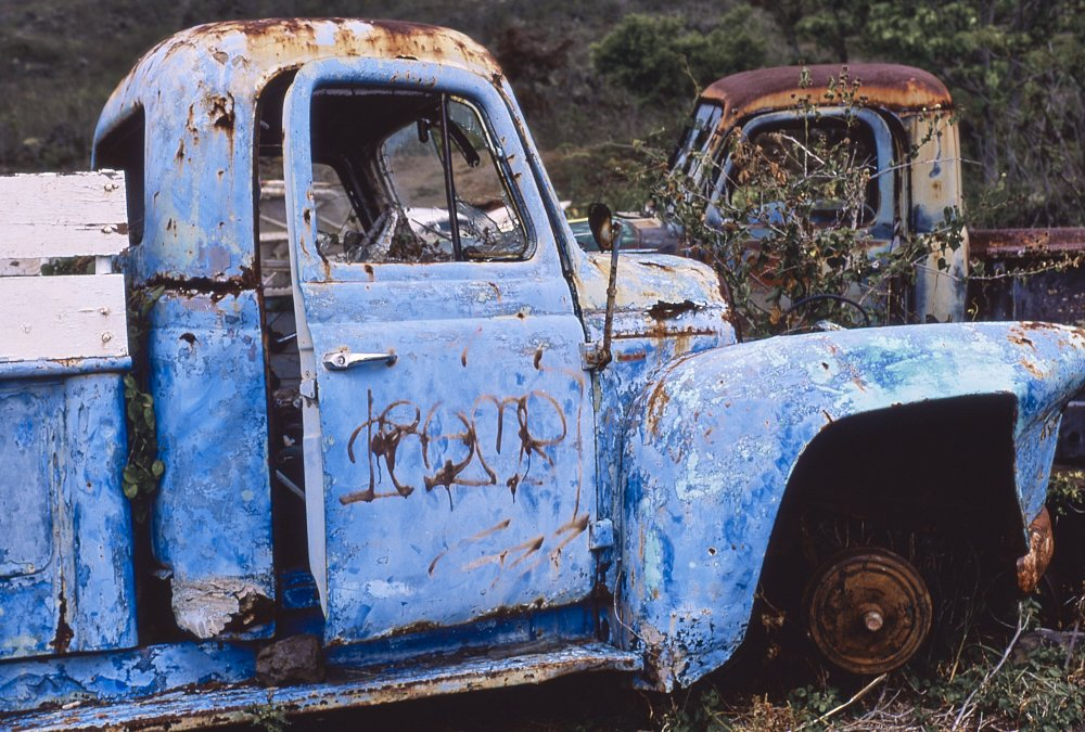 Horizontal photo of a 1940s vintage pickup truck that has been abandoned on the island of Maui, Hawaii. The photo was taken from the right side of the truck, with the front of the truck pointing to the image's right. The truck's bulbous rounded cab appears just large enough for two people. The right front tire has been removed underneath the fender. A rusted wheel sits directly on the ground. The truck's patchy blue paint—light sky blue to a deep azure—makes the truck pop against the dark brown and green hillside in the background. Dark brown rust spots punctuate and accent the blue exterior. In the top right corner of the photo the cab of another abandoned truck, visible over the blue truck's fender, faces the opposite direction—as if two lonely friends sit silently together.