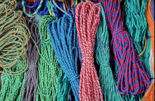 Close-up landscape photo of 10 braided plastic ropes laid out in a row at the Chichicastenango market, Guatemala. Each rope is about ¼-inch thick—looped and tied in the middle, with the loops at the top and bottom of the image. We see a rainbow of color combinations: orange and green, green and yellow, light and dark blue, red and white, red and blue.