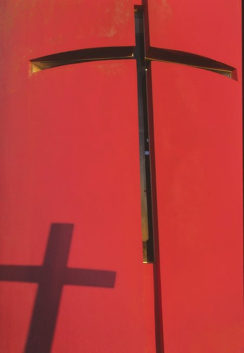 A vertical photo of an exterior church wall in Huatulco, Mexico. The wall is painted bright red, which glows brightly in the early morning sunrise, as the sun tips over the horizon. A window in the shape of a crucifix, constructed of narrow 4-inch glass strips, angles from the bottom right third of the image and extends to the top where it intersects at the center edge. The window's glass is set several inches back into the red stucco wall, such that we only see the dark shadows of the cross in the window, due to the angle of the sun. In the lower third of the image, we see another shadow of a crucifix mounted somewhere in the church's front lawn. The cross-shadow points toward the upper center of the photo. Two cross-shadows angled onto a bright red wall in the morning sun.