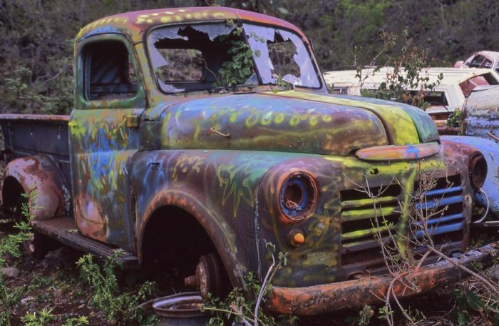 Horizontal photo of an abandoned 1950s truck on the island of Maui, Hawaii taken from the right front side of the vehicle, about 10-feet distant. The truck's surface is covered with rust. Some would-be graffiti artist has spray painted various random designs on the front grill, hood, and cab—stars, circles, swirls, and stripes—with yellow, blue, green, and red paint. Both headlights are long gone, as are all the tires. Rocks have been thrown through the front window, which angles back slightly from a vertical center fold, leaving shards of broken glass around the edges.