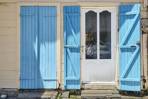 Horizontal photo of a white door with full-length blue shutters on either side in coastal town of Grand-Bourg on Marie-Galante Island in the Caribbean. Two full length panes of rippled glass divide the white door, which appears in the right side of the image. The long shutters on either side of the door are built with narrow planks of wood, framed with two Z-shaped supports that zig zag across the inside of the shutters. The Z-shaped pieces of wood cast deep shadows in the overhead sun. To the left of the door and its open shutters we see another set of blue shutters which are closed. The exterior wall has been painted a light beige.