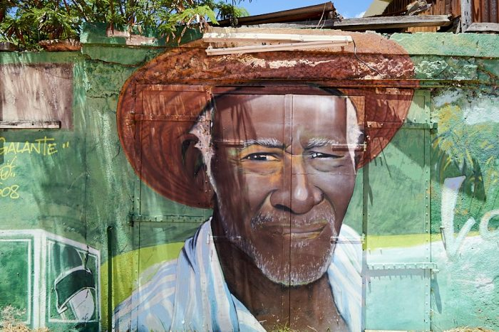 Horizontal photo of an artist's mural painted on the side of a building in the town of Grand-Bourg on the island of Marie-Galante. The mural is a portrait of a black man who appears to look directly at the camera's lens. He squints into the direct sun, lips drawn tightly, giving the appearance of a mild grimace. White hair, white eyebrows, and white beard stubble frame his long face underneath a reddish-brown straw hat which is folded up above his forehead. His leading right shoulder dips forward slightly. An open shirt, with large light blue and white vertical stripes, opens to his black-skinned chest. Multiple colors of green: pastel teal, lime, mint, olive, and pine, surround his head and shoulders. A metal door comprises most of the building wall. Hinges, strips of metal brackets, and rivets define the mural's background texture. At the top of the photo weathered 2x4s and a rusted corrugated roof protrude above the top of the building.