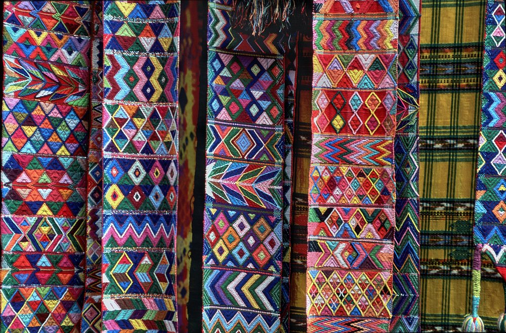 A close-up photo (landscape layout) of colorful cloth belts hanging vertically at the Chichicastenango market, Guatemala. The embroidery on each belt is extremely finely stitched, showing off significant detail in each piece. Patterns include diamonds, zigzags, Xs, chevrons, stripes, and more. Most of the belts are multicolored—with every color imaginable in the color wheel.
