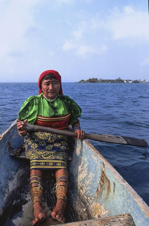 This vertical (layout) photo shows a Kuna Yala woman in the Guna Yala region of Panama. Sitting in the bow of an old dugout canoe she faces astern, from where the photo was taken. Her red scarf covers black hair as she stares intently at the camera with an expressionless face. She wears a green blouse with Kuna molas wrapping her waist, and a dark blue skirt imprinted with detailed yellow patterned designs. Both hands hold an old cracked wooden paddle which hangs over the side of the boat. Her legs, wrapped with purple and yellow beads, stretch bare feet forward toward the camera. Blue sky and ocean comprise the background, with a small flat island off in the distance on the right side of the image.