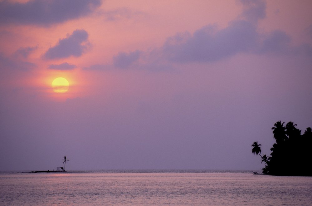 This horizontal landscape photo shows a sunset in the Guna Yala region of Panama. Taken from the deck of an anchored sailboat, ocean comprises the lower 1/5th of the image. The balance of the image consists of a wall of lavender-colored clouds with a yellow setting sun peeking through the scattered cloud layers in the left upper third. The ocean below reflects the sky's lavender, yellow, and gold colors in a blended palette of pastels. In the lower right bottom of the image we see the edge of a small island, its palm tree outline silhouetted black against the lavender sky.