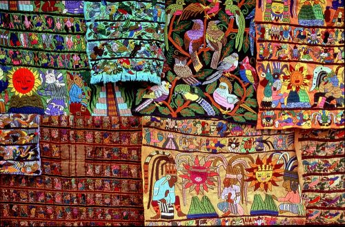 Close-up (landscape layout) photo of eight different multicolored tapestries hanging on a rack in a Santiago Atitlan marketplace, Guatemala. Each tapestry displays rows of multicolored Mayan-themed iconography and images depicting birds, suns, volcanoes, pyramids, priests, and Mayan gods. Four of the tapestries have beige or brown backgrounds, two are dark green, and one is a bright sky blue. The detailed embroidery work portrays its subjects in significant detail.