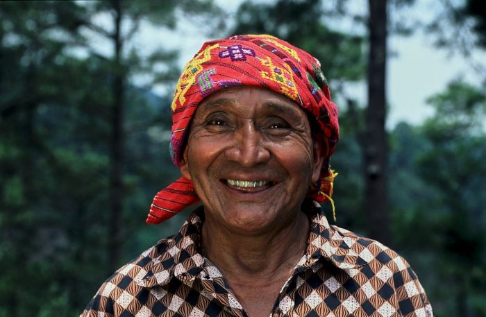 Close-up landscape photo head and shoulder portrait of a Guatemalan shaman on a mountainside in Chichicastenango. He is centered in the shot, with blurred dark green trees in the background on the left and right third of the image. The light is soft and diffuse. His shirt prominently displays a 1-inch diagonal checkered print with an unusual combination of colors: black, white, and light coral. He wears an embroidered red headscarf, with accents of yellow and purple, tied at the back of his neck. He smiles broadly at the camera, showing off two silver capped upper teeth.