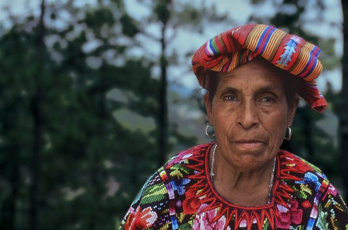 Close-up landscape head and shoulder photo portrait of a Guatemalan shamaness on a mountainside in Chichicastenango. The composition shows her on the right side of the image, with the left side comprised of blurred dark green trees in the background. The light is soft and diffuse. Wearing a traditional brightly colored embroidered blouse with multicolored pink, red, and blue flowers—and a similarly multicolored tapestry folded onto her head—she looks directly at the camera. Her jewelry consists of 1-inch looped silver earrings and a necklace with clear glass beads.