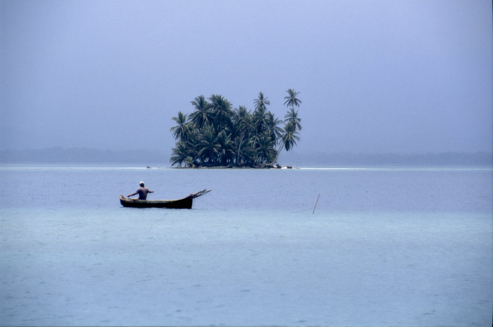 This landscape photo, from the Guna Yala region of Panama, shows dark powder blue water below the horizon, in the middle of the image; and a similarly dark powder blue sky—all through the filter of an imperceptibly light fog. In the middle of the photo, at the horizon line, a small round island is visible. The island is 150-200 feet away, and maybe another 100-feet in diameter. A cluster of dark green and dark teal palm trees rises from every inch of the island, 50-60 feet high. Intersecting the lower left third of the image we see a dugout canoe which is almost parallel to the lens. The stern is slightly more distant than the bow, which is tied to a stick jutting out of the water two canoe-lengths to the right. A fisherman sits in the canoe, his back to us, arms stretched out sideways, as he manages the fishing line.