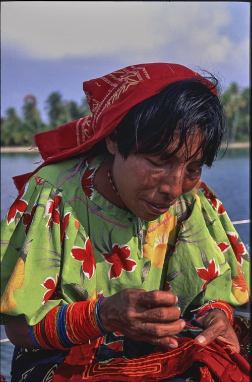 A vertical head and shoulder portrait of a Kuna woman in the Guna Yala region of Panama. A red cotton scarf covers medium-length black hair. She wears a lime-green blouse with large red and yellow flowers which is lit in the dazzling sun. Bright red and blue beads wrap tightly around her forearms from wrists to below her elbows. A long, thin black vertical tattoo traces from the tip of her nose to her forehead. She looks down at her gnarled hands are she sews a Kuna mola. Equal parts of sky, island, and ocean blur the background.