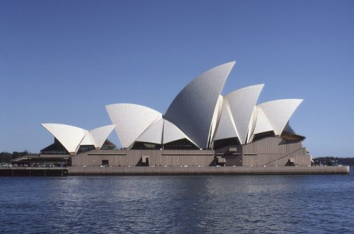 Side view of the Sydney Opera House in front of a cloudless blue sky, showing all of its white concrete sail-shaped roof sections. Image taken from a boat on Sydney Harbor. Sydney, Australia.