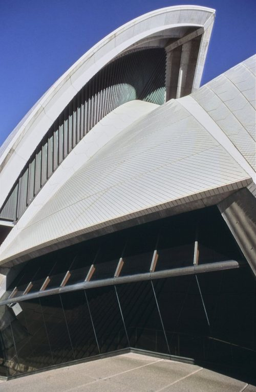 Medium shot of a roof sail section and glass windows of the Sydney Opera House taken from the steps leading to the forecourt area. Top roof sail is framed by clear blue sky. Shows exterior construction detail.