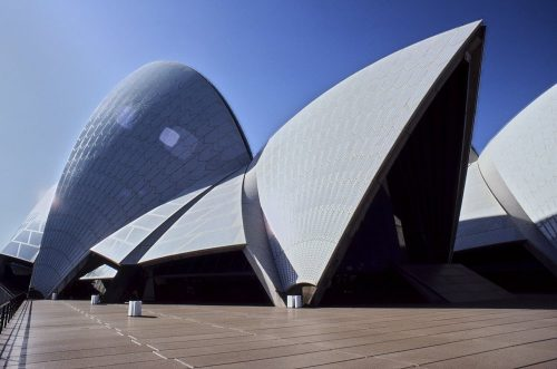 Medium shot of a roof sail section and glass windows of the Sydney Opera House taken from the front promenade. Roof sails are framed by clear blue sky. Shows exterior construction detail.