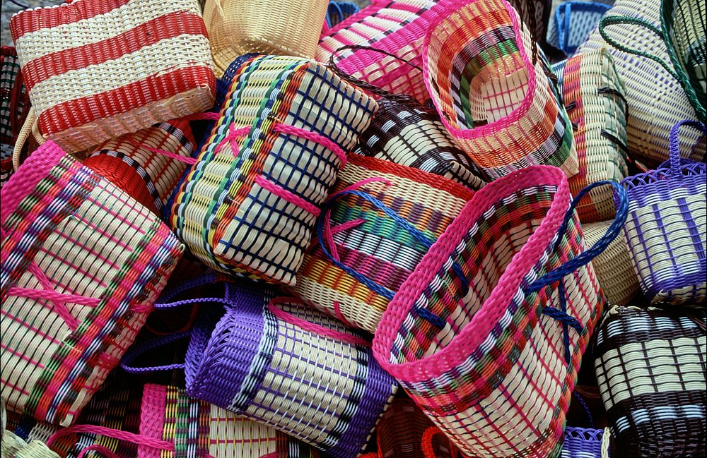 A medium shot photo (landscape layout) showing a stack of 15-20 plastic multicolored woven baskets for sale at the Chichicastenango market, Guatemala. The oval-shaped baskets measure 1-2 feet in width. They have been thrown into a disorganized heap: sideways, right-side up, and upside down. Each basket's color combination is different, and colors are wildly mixed: pink, white, red, green, yellow, orange, black, and purple.