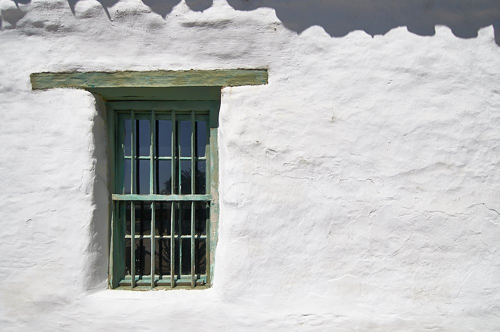 A horizontal landscape photo of a white stucco wall in Old Town, San Diego. The wall is brightly illuminated by the full-on overhead sun. A vertical window intersects the left third of the image. Framed with weathered wood painted olive-green, the narrow 3-foot wide window is centered underneath a six-foot long lintel, which is embedded into the stucco wall. The olive-colored lintel and window contrast dramatically against the white stucco wall. At the top edge of the image, shadows from the Spanish style tile roof (which is not visible) frame the upper edge of the photo in a narrow strip along the horizontal length of the white wall.