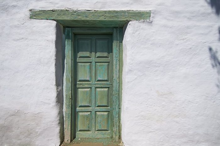 A horizontal landscape photo of a white stucco wall in Old Town, San Diego. The wall is brightly illuminated by the full-on overhead sun. A vertical door, just left of center, is framed with weathered wood painted shades of olive and teal green. Above the door a six-foot long lintel is embedded into the stucco wall. Eight rectangular panels, carved into the door, cast shadows below each panel. The olive-teal colored lintel and door contrast dramatically against the white stucco wall. At the right side of the image, shadows from a nearby tree frame the edge of the photo in a narrow strip along the vertical length of the white wall.