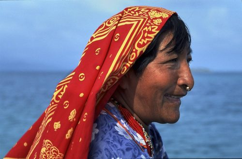 Landscape portrait of a Kuna woman in the Guna Yala region of Panama. We see the right side of her face, which is exposed to the sun, as she gazes off-camera to the right. She smiles happily. A gold nugget, which glints in the sunlight, pierces the lower part of her nose. On her head she wears a long red cotton scarf, with yellow accents, which trails off her shoulders and below the image frame on the lower left. Bangs hang down from underneath the scarf and sweep across her forehead. She also wears a light blue cotton blouse with white and darker blue floral prints—and a necklace of tiny red beads looped into multiple stranded layers. Behind her a blurred ocean and sky forms a solid blue in the distance.