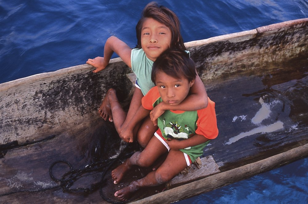 This landscape photo, taken in the Guna Yala region of Panama, looks down into a dugout canoe at two Kuna children. The canoe slices the rectangular image at almost a 45-degree angle, from upper right to lower left. Sitting in the canoe, a sister and brother look up at the camera, curious but unsmiling. The eight-year-old sister steadies herself with her right hand on the starboard gunwale, her left arm around her younger brother, who is perhaps six years old. They both wear shorts and T-shirts, and their legs and knees are scuffed with dirt. She wears a light turquoise sleeveless T-shirt. Her brother wears a green T-shirt with a bright orange collar and orange sleeves down to his elbows. They wait for their father, who is selling us fruits and vegetables onboard our sailboat. The inside of the canoe has small puddles of water. At the top and bottom of the frame we see deep blue water of the Caribbean Ocean.
