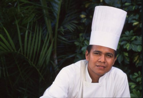 This landscape portrait of a chef in San Salvador, El Salvador, shows him in a double-breasted, white chef's uniform. He is a young, handsome El Salvadoran man in his late twenties. He faces the camera directly. In the bottom of the frame, we see his torso just above his elbows. His right shoulder is positioned just below center in the image. He leans to his left, such that his face is in the right 1/3 of the frame. He wears a 2-foot-high white chef's hat that leans upward and to the right at a 25-degree angle. Dark green tropical foliage blurs in the background on the left side and right edge of the photo, making his white uniform and conspicuously tall hat pop in the foreground.
