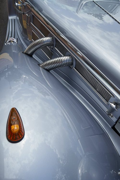 Vertical closeup photo of a Mercedes Benz 1937 540K Special Roadster's front hood. The image is taken from the front left side of the vehicle looking down to the fender and hood. The most prominent feature in the image is the front left fender in the lower left half of the photo: a smoothly curved silver paint metal that forms a large tear-drop shape. Looking down into the highly polished fender we see diffused images of clouds in the sky. In the lower left corner, on top of the fender, an orange teardrop turn signal light contrasts against the silver fender. The fender sweeps back like a ski jump to the mounting step at the top left of the image. Above the fender several lines of chrome trim and a chrome mesh grill cuts at a 45-degree angle from the top left of the photo to the bottom right. Two shiny 3-inch corrugated chrome metal pipes protrude from the mesh grill. The pipes sweep backwards and re-insert into the large silver painted fender. The silver hood reflects more clouds in the top right of the image. Without knowing this is a vehicle, the image appears to be an abstract of a highly polished art deco machine.