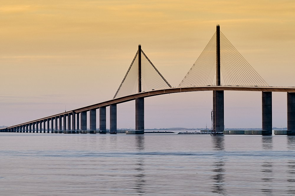 Horizontal photo of the Sunshine Skyway Bridge that spans the entrance to Tampa Bay between St. Petersburg to the north (left), and Terra Ceia to the south (right). The bridge's distinctive cable-stayed supports rise like two gigantic sails 250-feet high over the 180-foot bridge height on the right two-thirds of the image. (Total height 430-feet.) The sky behind the bridge, in the upper two thirds of the image, ranges from a muted grayish mauve on the horizon to a dusty mustard yellow at the top of the frame. Waters in the foreground reflect the gray-mauve horizon. On the left side of the photo, the bridge diminishes in perspective to a small point on the horizon.