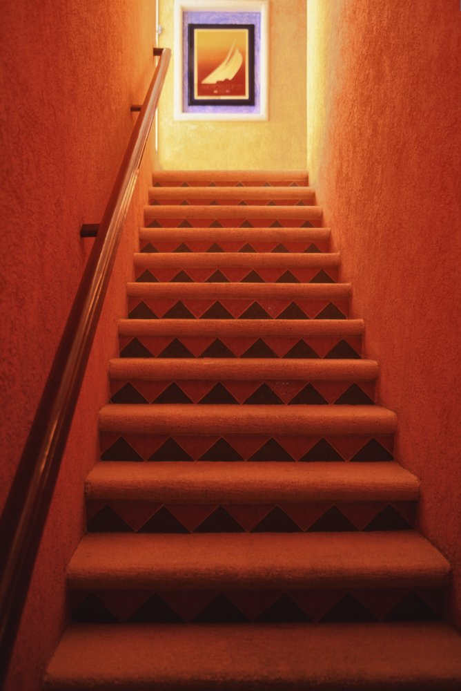 A brightly lit vertical photo, taken from the bottom of a stairway with 12 steps, looks up to the top of the stairs. At the top we see bright light coming in from an invisible window off to the left of the landing. Bright yellow light illuminates the landing at the top of the stairs, which refracts down onto orange-colored walls and orange carpeted stairs below. On the wall at the top of the stairs we see abstract artwork of sailboat sails within a vertical white frame around it. Inside the white frame is a lavender rectangular border. Inside the lavender border is a black rectangular border. Inside the black border is a yellow rectangular border. Inside the yellow rectangular border, we see a gradient background—from solid yellow at the top to a solid red ocean with whitecaps at the bottom. The yellow-red background provides a backdrop to the orange sails bending in the wind. A brown varnished wooden banister, reflecting deep orange tones from the adjacent walls, reaches from the lower left bottom of the image to the top left, just in front of the landing.