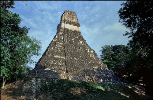Tikal, Guatemala. The Temple of the Giant Jaguar, fills the photo from the perspective of standing at ground level 200-feet distant, looking up 180-feet up the face of the steep pyramid to the high roof comb. Blue sky and white clouds provide a backdrop for the upper 2/3s of the temple, which is framed by green trees on both sides. Ten visitors walking along the base of the pyramid appear miniscule.