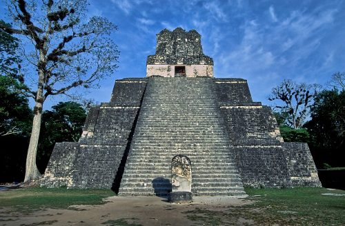 A straight-on photo of Temple II (Temple of the Masks), in Tikal, Guatemala. A steep 34-foot wide stairway, which dominates the photo, starts at ground level in front and ascends to the upper third of the image. The stairs are flanked by three foundation levels, built in thirds, from larger at the bottom to smaller at the top. A large 43-foot high roof comb projects up from top platform. Two people sit inside the doorway of the roof comb, facing the stairs. The pyramid is framed by blue sky at the top, green grass at the bottom, and trees both left and right.