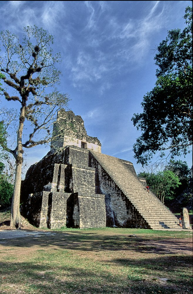 Tikal, Guatemala. Temple II (Temple of the Masks) fills the photo from the perspective of standing at ground level looking at the pyramid's left-front corner. A long flight of steep stairs starts at the lower right of the image and climb at a 45-degree angle to the left in the center. The temple is framed by blue sky and white clouds at the top, green grass t ground level, and a few trees both left and right. Sun fills the temple face and stairs, as a lone figure in a red shirt scrambles up the steep steps.