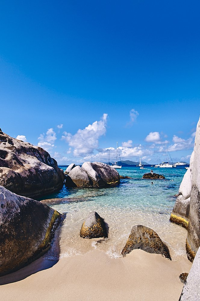 Deep blue sky frames the upper half of this vertical photo of The Baths in the British Virgin Islands. White cumulus clouds form a puffy strip across the middle of the photo, just above the horizon line. Sailboats at anchor from another stripe of white just below the clouds. Beige sand, damp from a receding wave, fills the foreground. Huge boulder stacks, on the left and right side of the photo, reach half-way up into the image, and 100-feet out into the water. Crystal clear rippled wavelets cover the beige sand in the middle of the photo, stretching out into turquoise waters of Devil's Bay.