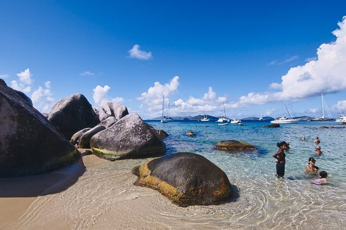 Deep blue sky frames the upper half of this horizontal landscape photo of The Baths in the British Virgin Islands. White cumulus clouds arc from the upper left, down across the horizon, and up again to the right. Beige sand fills the lower third of the image, while large boulders cascade from the left into the center. Crystal clear waters lap against the boulders and ripple out into the turquoise waters of Devil's Bay. Families swim in the shallow waters on the right side of the photo. Ten or more sailboats drift at anchor on the horizon, several hundred feet in the distance.