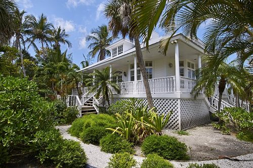 Landscape photo of a home on Useppa Island, Florida. The image was taken from the right and front of the house, at about a 30-degree angle and 40-feet distant. The white house—in the Key West architectural style—has an elevated porch which wraps around on all four sides. A small, windowed dormer can be seen in the center of a silver metal roof. The front stairs descend from the porch to a manicured pea-gravel walkway that extends toward the bottom of the image. Lush tropical palms and foliage in multiple shades of green frame all sides of the house, with blue sky and small wisps of white clouds overhead.