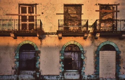 A landscape (layout) photo of a wall of an abandoned building in Panama City, Panama. Three boarded up doorways on the second story each have their own wrought iron balcony. Underneath the three upper doors are three more doors on the ground floor. Teal colored stonework frames each of these doors on both sides and a keystone arch overhead. The ground level doors have wrought iron fences barring access. Paint on the beige-colored stucco wall cracks, flakes, and peals with age. The setting sun casts golden light on the upper 2/3s of the image, while the lower 1/3 is in a softer golden shadow.