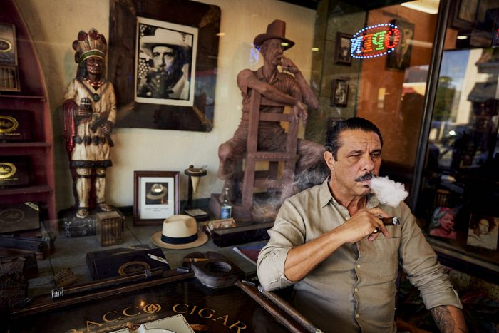 A horizontal photo of Pedro Berro, owner of Cuban Tobacco Cigar Company, who sits in front of his store in Little Havana, Miami. As he smokes one of his cigars, his right elbow rests on a square table with the name of the store visible on the surface. His right hand holds a dark, fat, ash-laden, lit cigar inches below his chin. He stares at a 45-degree angle toward the right side of the image as he exhales a small cloud of dense white smoke. Behind him, through the glass window of the storefront, visible above Pedro and to the left, a full-size wood carving of a man sits facing backwards on a simple chair. The man rests his right arm on the top of the chair as his left arm, bent at his left elbow, holds a wooden cigar to his mouth. The statue's pose, actions, and direction of his gaze almost perfectly mirror Pedro. We see additional cigar-related paraphernalia in the window adjacent to the statue: a B&W photograph of another man smoking, what appears to be the straw hat of the man in the photo on the surface below, and another, smaller, wooden statue of an Indian chief with full headdress holding a cylindrical collection of cigars in his right hand. The Indian stares off in the same direction as Pedro and the other statue.