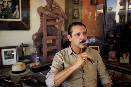 A horizontal photo of Pedro Berro, owner of Cuban Tobacco Cigar Company, who sits in front of his store in Little Havana, Miami. As he smokes one of his cigars, his right elbow rests on a square table with the name of the store visible on the surface. His right hand holds a dark, fat, ash-laden, lit cigar inches below his chin. He stares at a 45-degree angle toward the right side of the image as he exhales a small cloud of dense white smoke. Behind him, through the glass window of the storefront, visible above Pedro and to the left, a full-size wood carving of a man sits facing backwards on a simple chair. The man rests his right arm on the top of the chair as his left arm, bent at his left elbow, holds a wooden cigar to his mouth. The statue's pose, actions, and direction of his gaze almost perfectly mirror Pedro. We see additional cigar-related paraphernalia in the window adjacent to the statue: a B&W photograph of another man smoking, what appears to be the straw hat of the man in the photo on the surface below adjacent to a photograph of the same hat.