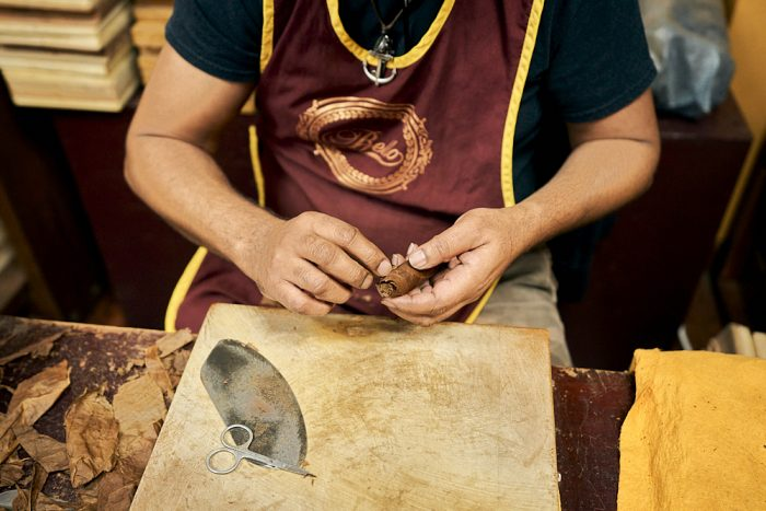 A horizontal photo of a man hand cutting and rolling dried tobacco leaves at the Cuba Tobacco Cigar Company in Little Havana, Miami. The man, sitting, faces the camera. We see his chest, arms, and hands. He wears a black T-shirt covered by a maroon-colored apron with gold trim on the sides and around the U-shaped neck. He holds an almost finished, wrapped cigar in his left hand as he uses his left hand to adhere the loose edge of a leaf to the tip of the cigar. The worker's fingers are stained brown from working with the tobacco leaves. He works over a plastic cutting board—its cracks and cervices also stained brown from the dark, dried leaves. On the left side of the cutting board a small pair of stainless steel trimming scissors lies atop of an oval-shaped steel cutting blade. Discarded tobacco leaf remnants cover the chipped, wooden table on the left and right side of the cutting board.