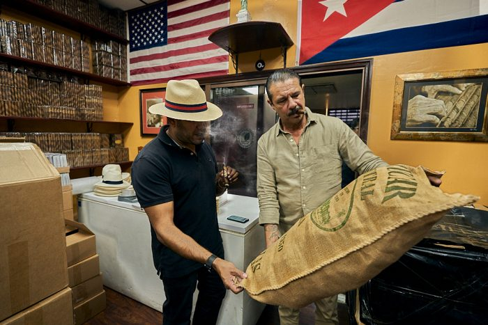A horizontal photo of two men standing adjacent to each other while inspecting a large burlap sack of tobacco leaves. The man on the right holds the bag at a 45-degree angle, such that the man on his left can view the large printing on the surface. The man on the left reaches down with his right hand to hold the bottom of the bag to improve his angle of view. Both men smoke as they inspect the label, blowing puffs of dense white smoke. The man on the left wears a straw fedora had with a straight 3-inch brim and a red and black hat band. Above them on the back wall we see a United States flag, with the flag of Puerto Rico adjacent to the right. On another wall visible to the left, rows of cigars packaged in cellophane sit neatly stacked on dark wooden shelves.