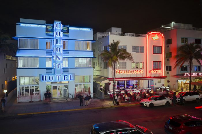 Taken from a drone at night hovering at 30-feet over Ocean Boulevard in South Beach, Miami, the Colony Hotel and Boulevard Hotel fill most of this landscape image. Baby blue lights illuminate the Colony's façade, and blue neon outlines the letters on the hotel's inverted-T sign, with the word 'Colony' reaching vertically from the second story to the roof. Boulevard Hotel's red neon vertical outline and red neon sign contrasts dramatically with the Colony's softer blue theme. Black sky and the dark street frame both hotels in the image.