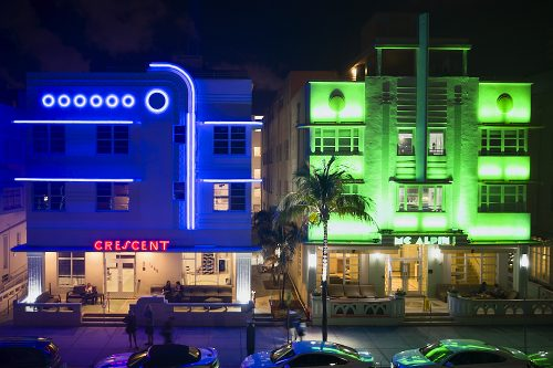 "A horizontal drone photo on Ocean Drive in Miami's South Beach at night, taken 30-feet in the air from the park across the street. A dark, deep purplish-blue light cloaks the three-story Crescent Hotel on the left—accentuated with blue neon art deco accent lights: Seven blue neon circles in a row hover just below the flat roofline. Horizontal blue neon lights line the tops of the windows on the second and third levels. On the right third of the façade, a pair of blue neon lights rise vertically from the portico to the roof, curving 90-degrees left over the blue circles. The Hotel's name, ""Crescent,"" blazes in red neon art deco letters centered over the first-floor portico. Adjacent and to the right, Mc Alpin's three-story façade glows in a shimmering, amplified ultraviolet green. The illuminated 'Mc Alpin' sign, centered over the portico, blazes in an intense lime green over the entrance. Both façades look like art deco cubes: the dark blue Crescent on the left; bright green Mc Alpin on the right."