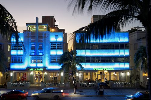 A horizontal drone photo on Ocean Drive in Miami's South Beach at night. Taken from 30-feet in the air, the image looks directly at the Mc Alpin and Ocean Plaza Hotels from the park across the street. Bands of bright blue lights illuminate the facades of both buildings, in between layers of windows on each of the three levels. Palm frond silhouettes frame the left and right foreground of the image. A pale lavender-gray sky fades to twilight behind the buildings. Car headlights and taillights streak by horizontally on Ocean Drive, captured by the long shutter.
