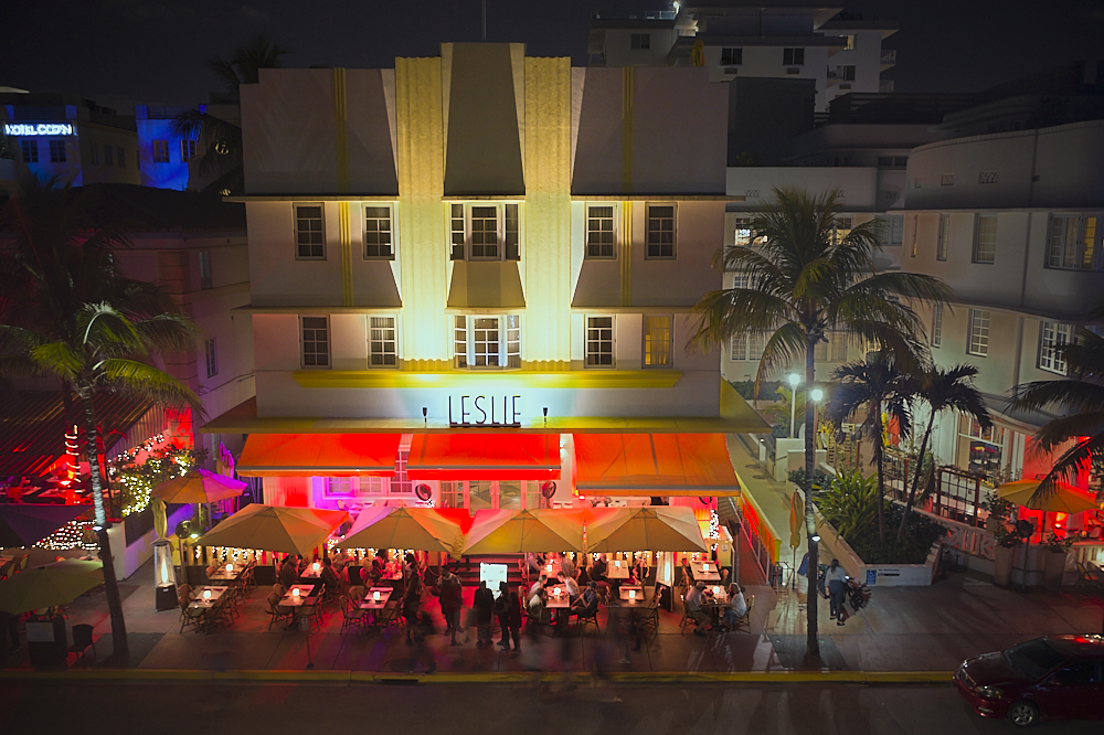This night shot of the Leslie Hotel on Ocean Drive in Miami's South Beach was taken from a drone hovering 40-feet across the street. Twin gold-lit vertical art deco fan facades reach from the second floor to the top of the roof. A red awning is brightly illuminated from the street level underneath, where tables are crowded with alfresco diners. A dark night sky and dimly lit street frame the building and outdoor dining scene top and bottom.