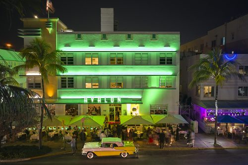 "A horizontal drone photo on Ocean Drive in Miami's South Beach at night. Taken from 30-feet in the air from the park across the street, the composition looks straight to the center of the Avalon Hotel. Bands of bright green neon lights stretch across each of the three-story balconies, in between a checkerboard of backlit and unlit windows. The hotel's signature ""Avalon"" horizontal sign, in large art-deco font, illuminates the front of the building's second story. Square yellow umbrellas line Ocean Drive where guests dine alfresco. A lone, white and yellow 57' Chevy convertible, with 4-inch whitewall tires and lots of 'attitude,' sits proudly, parked on the street. The polished hood and trunk of the Chevy glistens underneath the green lights of the hotel's façade."