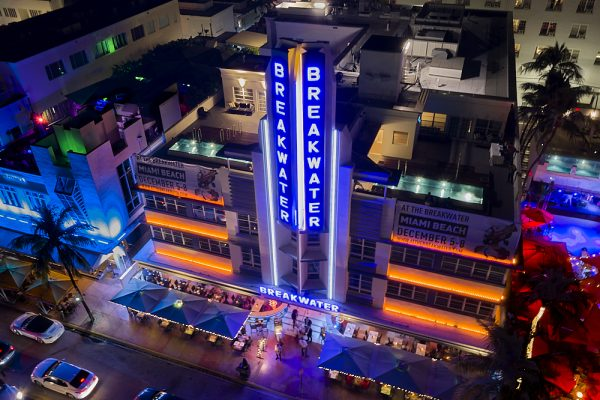 A horizontal drone photo on Ocean Drive in Miami's South Beach at night. Taken from 150-feet in the air, the image looks down to the Breakwater Hotel from the park across the street. The Breakwater's long vertical blue neon sign rises from the second story, reaching 50-feet or more over the top of building's 4-story frame. Two mint green colored swimming pools hug the front edge of the roof on either side of the large vertical sign. Orange neon horizontal lights outline the second, third, and fourth floors. On the street level far below, square awnings line Ocean Drive, where guests dine alfresco.