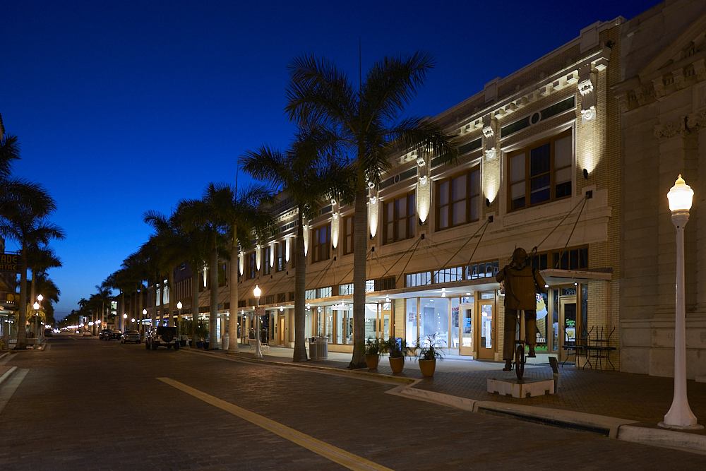 Looking northwest from brick-paved First Street in downtown Fort Myers, the faint light of an early dawn glows blue at the vanishing point on the horizon, brightening the dark sky overhead. Electric wall sconces illuminate the 2nd story of the building visible on the right side of the image, shining columns of light up towards the roof which highlights and accents the horizontal cornice along the roofline. Streetlamps and 30-foot palms line the street—the palm trees silhouetted by dawn sky. The street is empty and quiet except for metal sidewalk street art of a man balancing on a unicycle on the right side of the image.